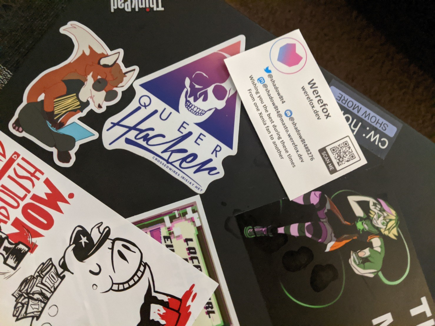 My thinkpad, decorated with stickers, including one of noted linux fox Xenia hunched over a laptop. Next to a Queer Hacker AOL logo sticker and a defund and abolish the police sticker.
